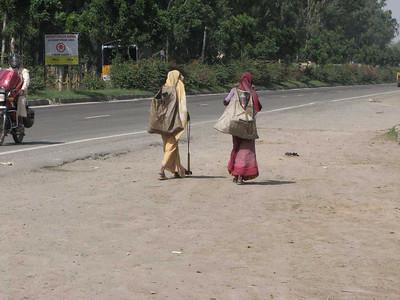 vrouwen op zoek naar afval langs de weg